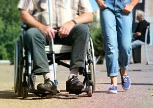 disabled man in a wheelchair being assisted by an OT